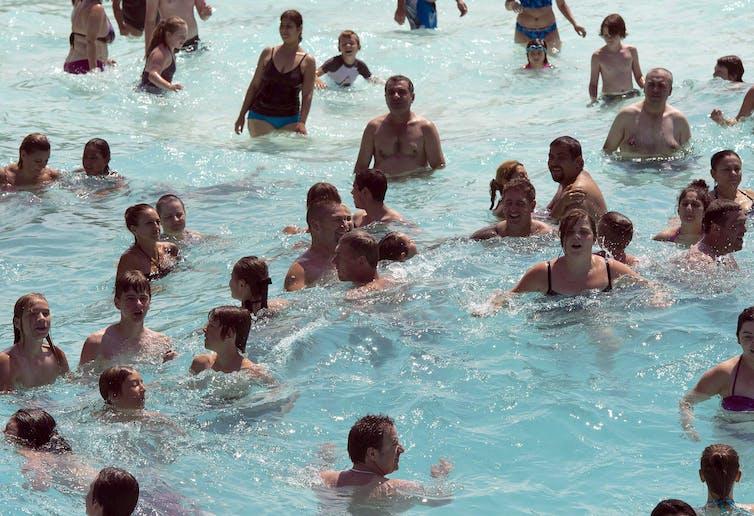 Des gens pataugent dans une piscine