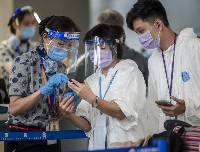 People wearing PPE look at a mobile phone