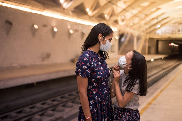 Mother and daughter listening to music and wearing a mask while waiting for train.