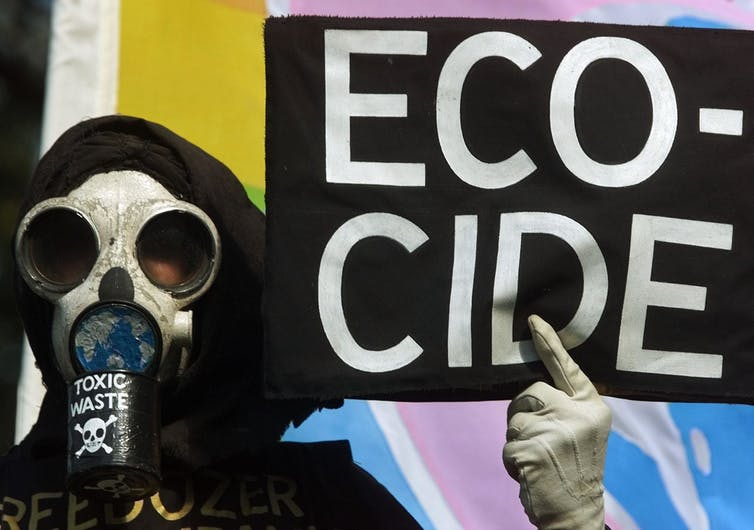 person in mask holds sign which says 'ecocode'