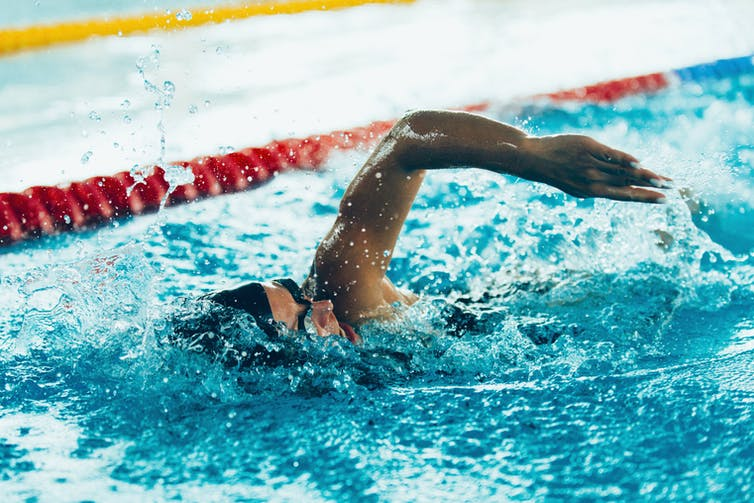 Person wearing a swim cap performs the front crawl in a swimming pool.