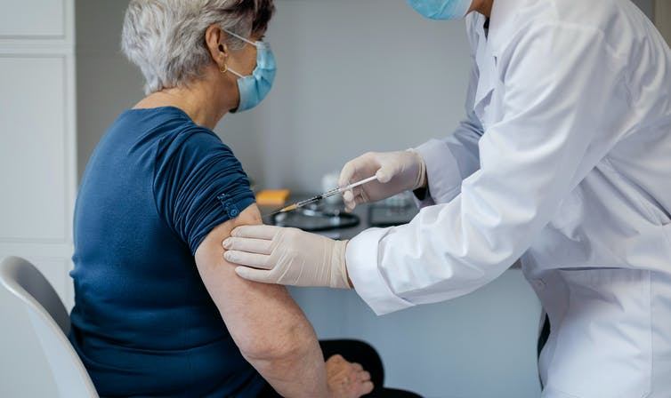 A woman being vaccinated against COVID-19