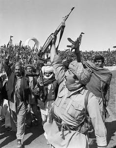 A group of fighters hold their guns aloft.