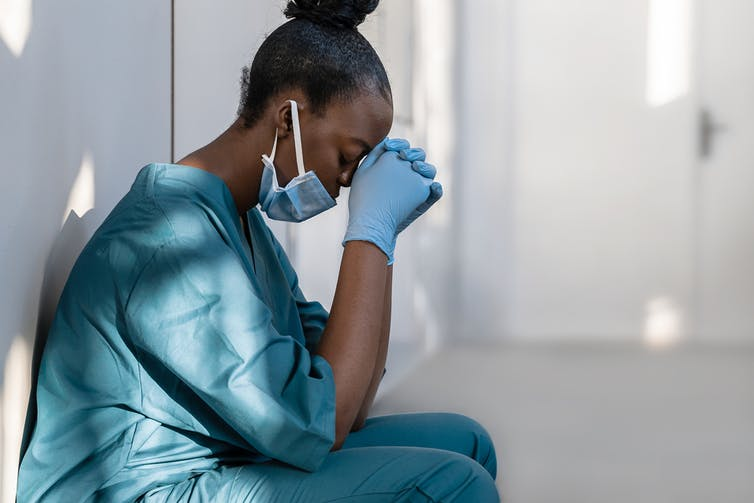 An exhausted looking COVID nurse leans against a wall, head in hands.