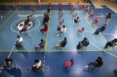 People sit in rows of chairs in a gym.