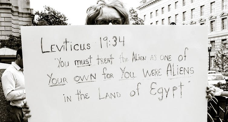 A person holds a sign that says Leviticus 19:34: