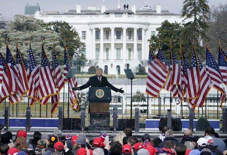 Un hombre de traje está parado con los brazos extendidos sobre una plataforma con banderas estadounidenses, frente a la Casa Blanca y una multitud de personas.