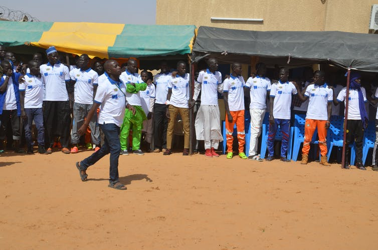 Un grupo de personas se toma de los brazos y se paran juntos en una línea mientras una persona camina frente a ellos.