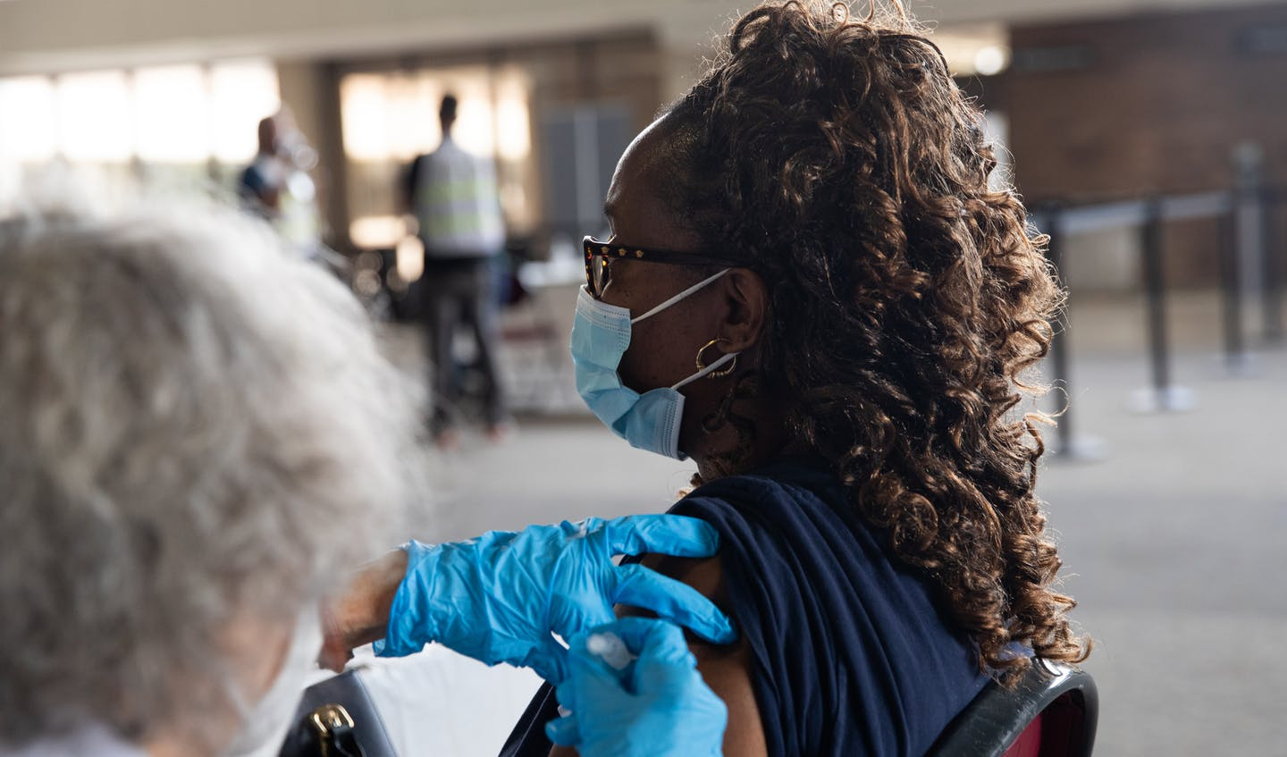 A woman wearing a mask gets a COVID-19 vaccine