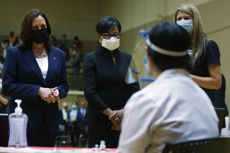 Vice President Kamala Harris, wearing a mask, meets with several people at a pop-up vaccination clinic.