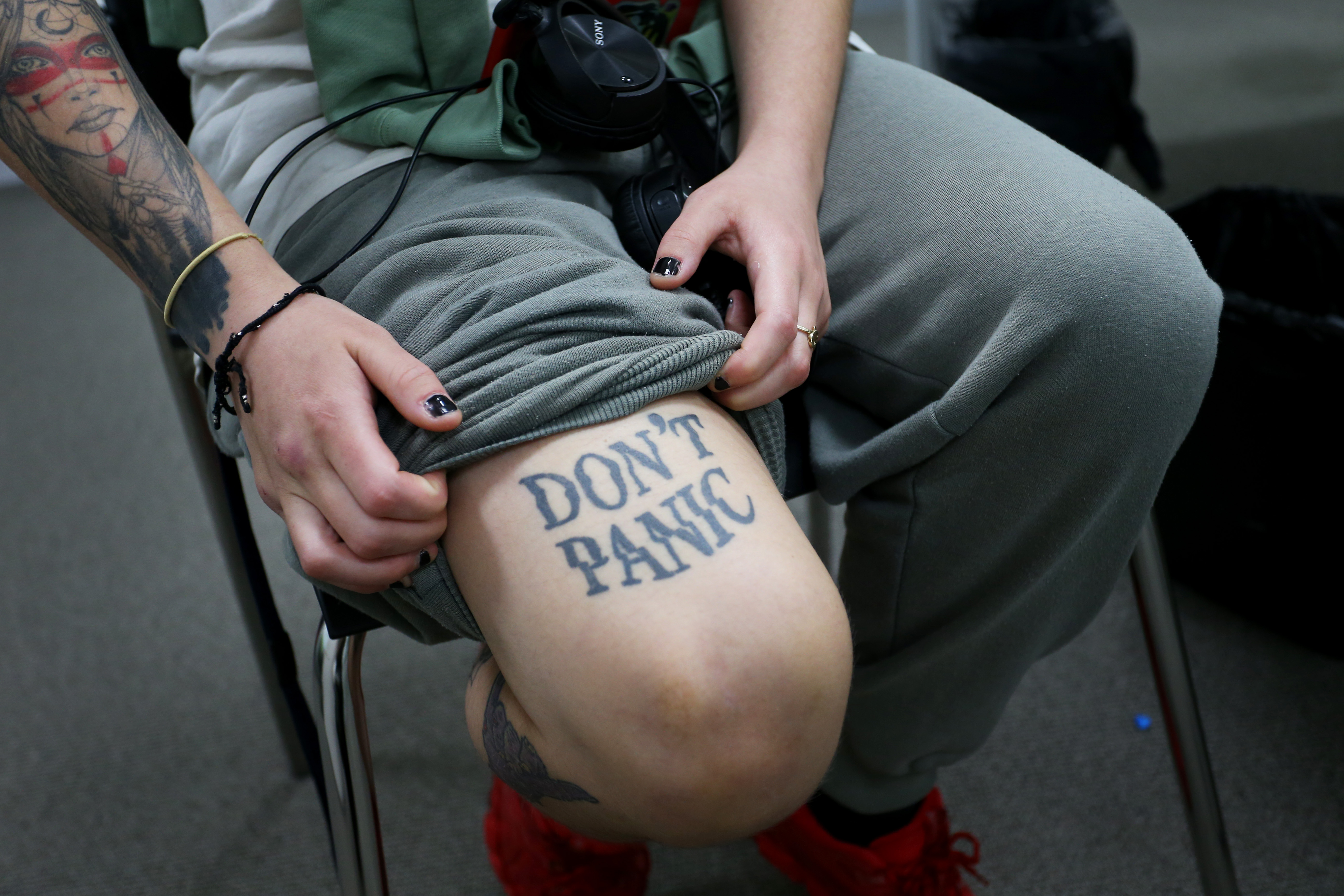 A woman shows off her pandemic tattoo that says, 'Don't Panic.'