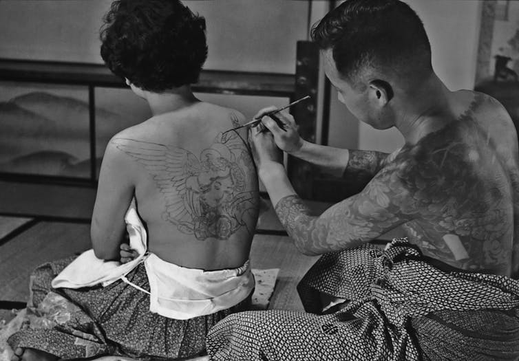 A Japanese tattoo artist at work on a design on a woman's back in Japan in 1955.