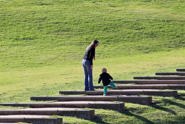 Mother and small child climbing steps.