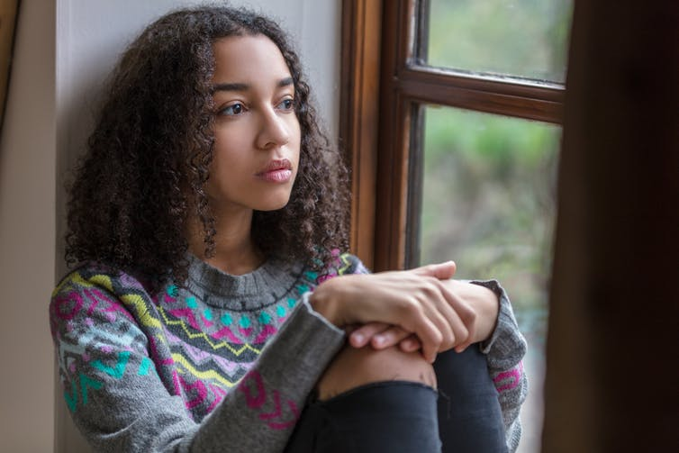 A teenage girl sits looking out a window.