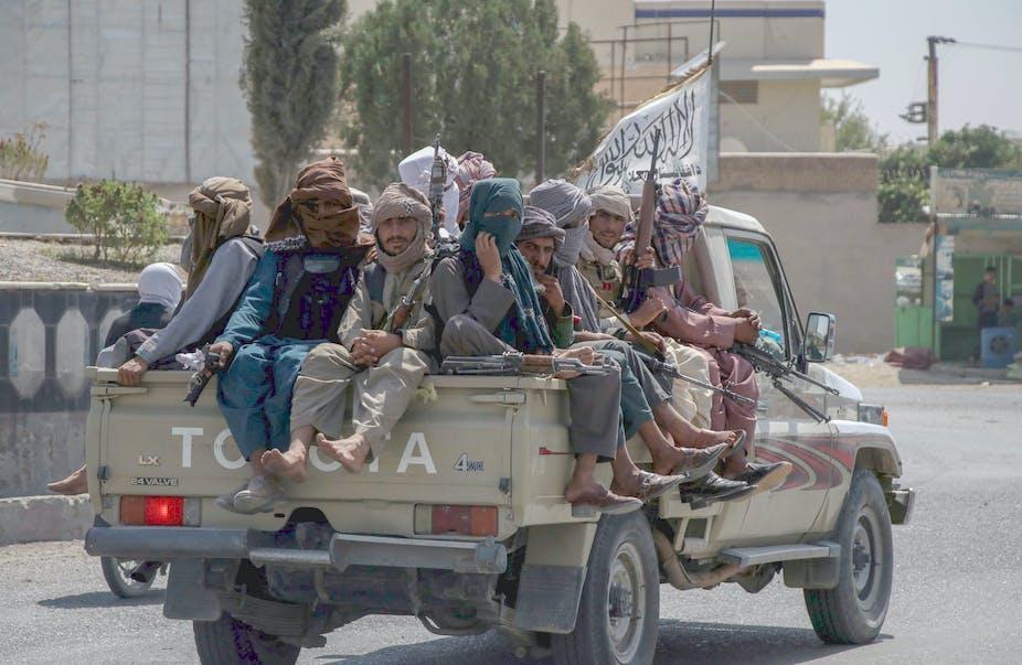 Taliban sit on back of pickup truck in Kandahar.