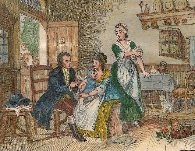 Coloured engraving of baby on mother's lap receiving a vaccine in England in the 1700s.