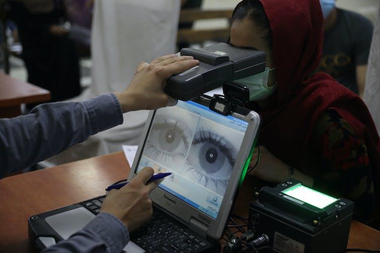 La pantalla de una computadora muestra una imagen ampliada de un par de ojos mientras un brazo sostiene un objeto en forma de caja frente a los ojos de una mujer que usa un pañuelo en la cabeza y una mascarilla.