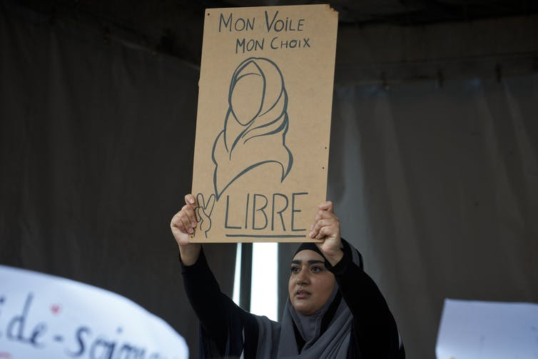 A woman in a headscarf at a protest in Toulouse, France, shows a drawing reading 'My veil, my choice, Free' in French.