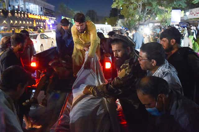 Volunteers and medical staff unload bodies from a pickup truck outside a hospital in Kabul.