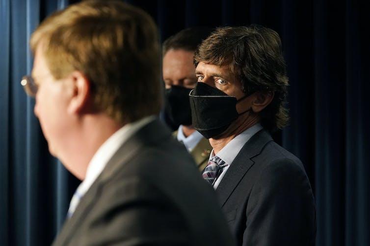 Man in mask eyes man in suit.