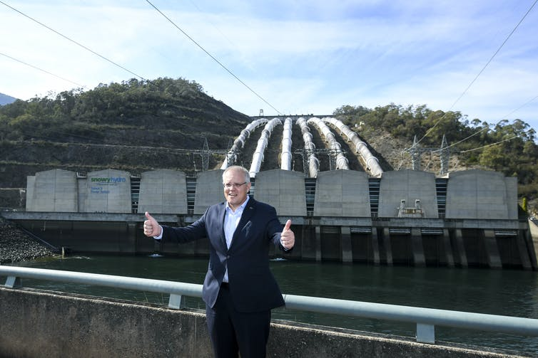 Man gives thumbs up in front of hydro project