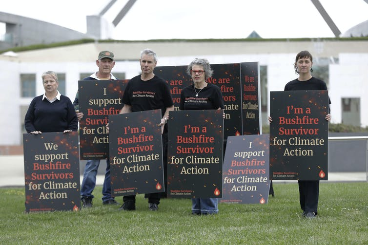 Bushfire survivors hold signs in front of Parliament House