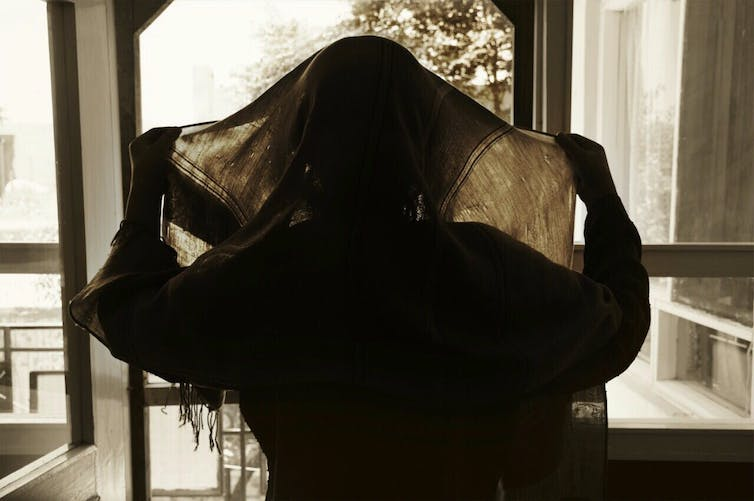 Silhouette of an Afghan woman wearing a head covering.