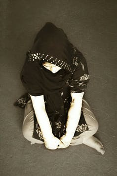 An Afghan women wearing a head covering sits cross-legged on the floor.
