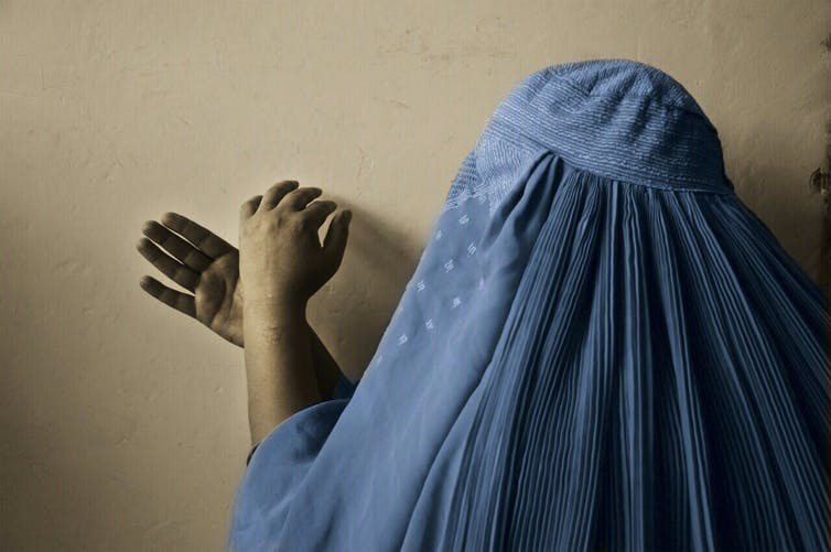 A woman in full burqa, anonymised, makes hand signs against a blank wall.
