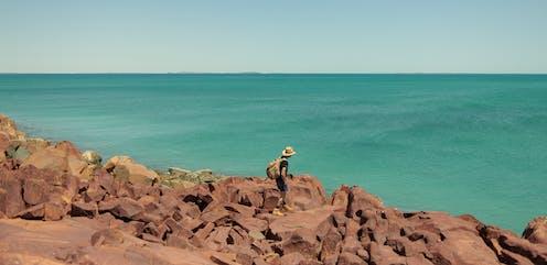 A man walking on rocks near the ocean.
