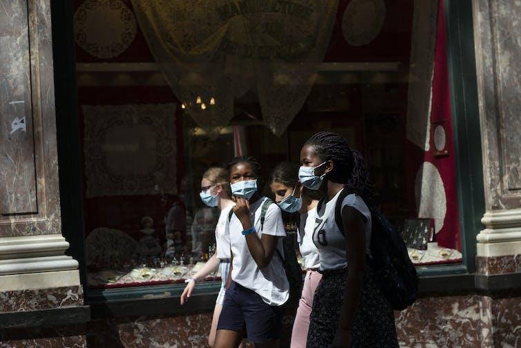 Des fillettes portant un masque marchent dans la rue
