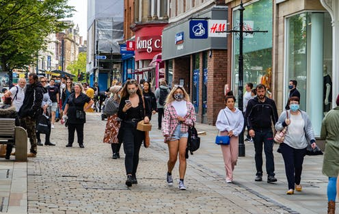 People walking down a shopping street in Manchester, UK