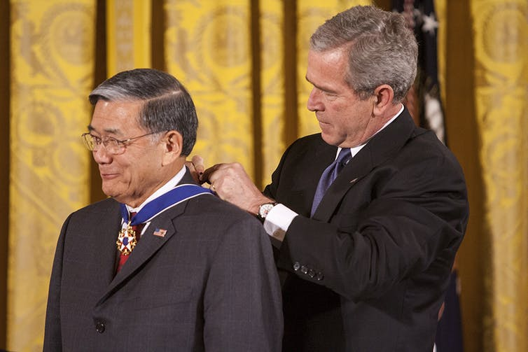 One man fastens an award ribbon around the neck of another man.