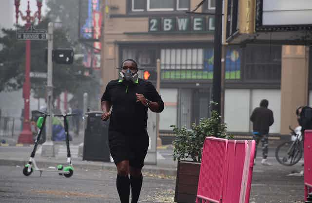 A young man wearing a respirator runs past stores in Portland
