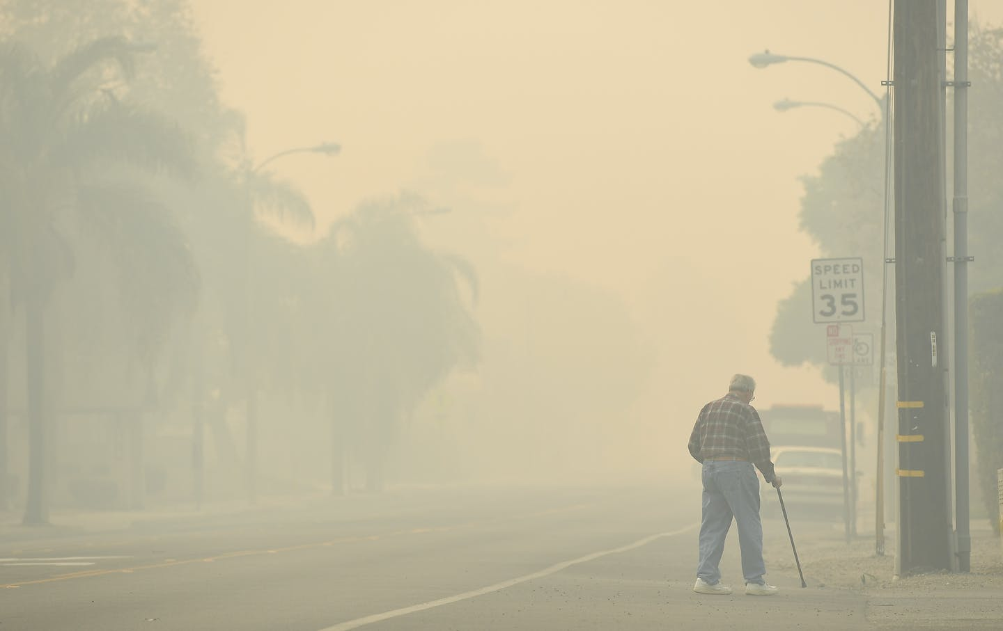 An older man with a cane crosses n empty road in smoky conditions.