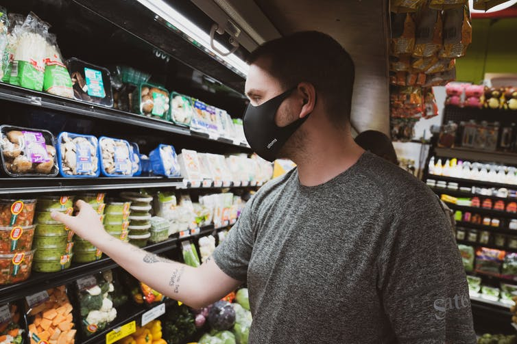 Man in a mask shops for dip.