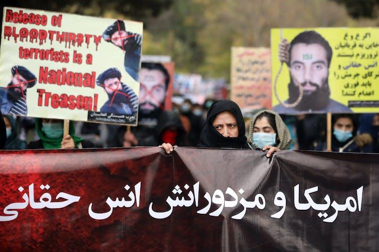 Des femmes afghanes brandissent des banderoles pour protester contre la libération de hauts dirigeants terroristes, dont Anas Haqqani.