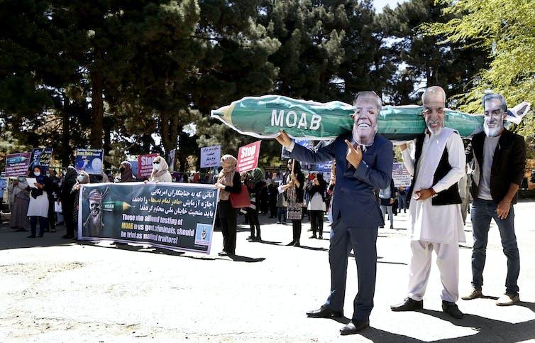 Des manifestants afghans portant des masques représentant Donald Trump, le président afghan Asraf Ghani et le vice-président Abdullah Abdullah après que les États-Unis ont largué la plus grosse bombe non nucléaire sur l'Afghanistan.
