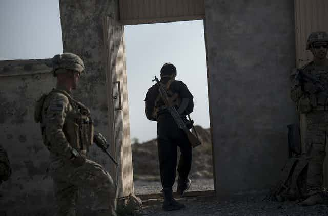 A member of the Afghan police and US soldiers leave a school that will be used as a polling station near Kandahar Airfield.