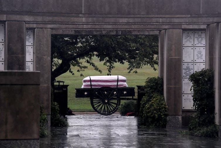 El ataúd de un soldado estadounidense se ve a través de una puerta durante una ceremonia de entierro con todos los honores militares