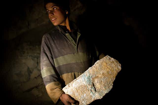 A young Afghan miner carries a large stone.