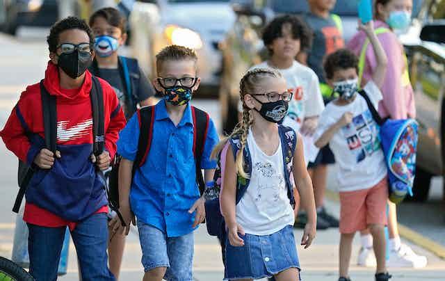 Children with backpacks walking to school.