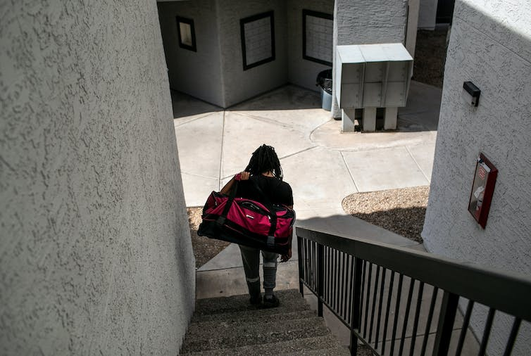 A person carrying a large duffel bag descends a staircase