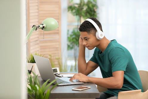 Jeune homme avec des écouteurs, penché sur son ordinateur portable