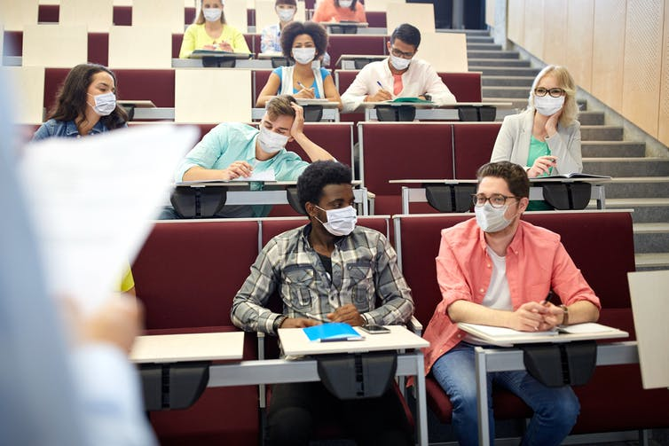Groupe de jeunes portant un masque, dans une salle de cours