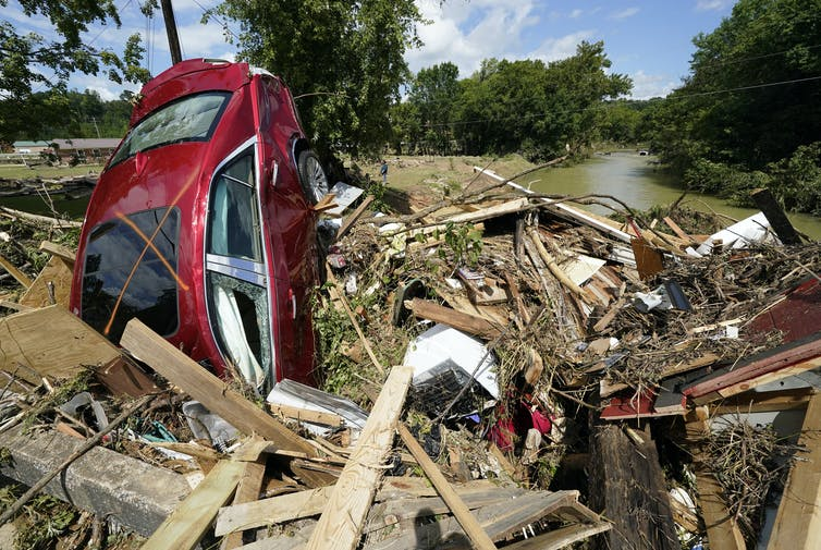 a wrecked car and other debris caused by a flood