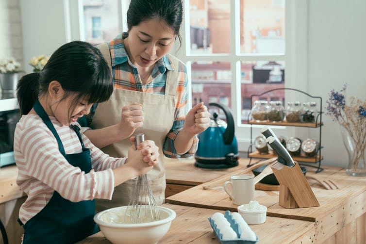 An Asian girl and mother bake.