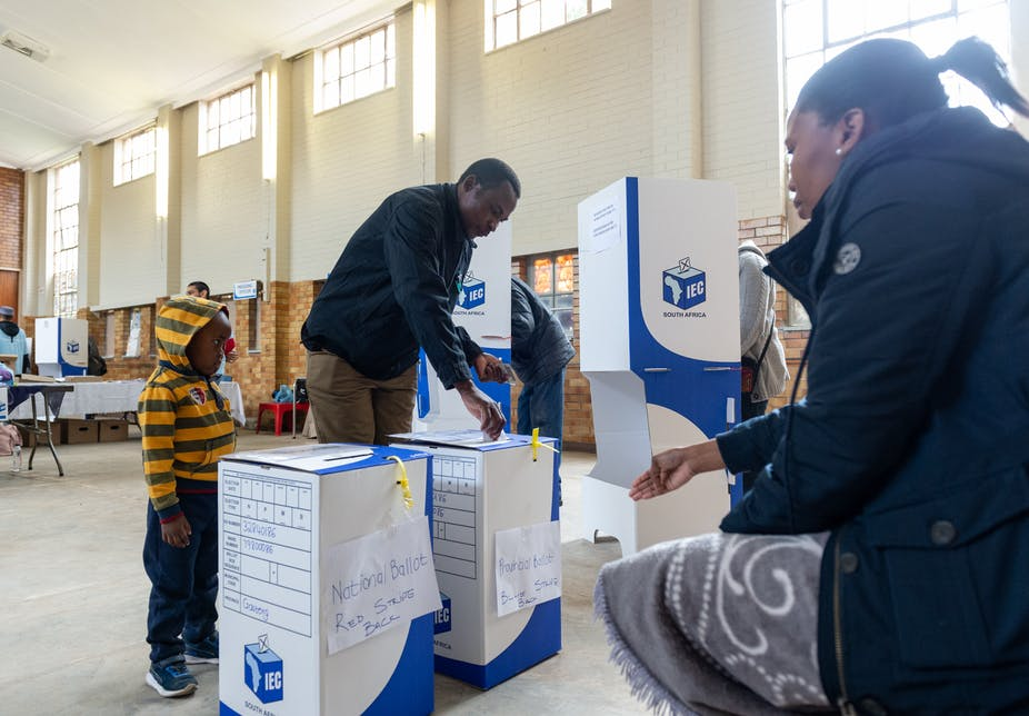 A man casts his ballot while a child looks on.