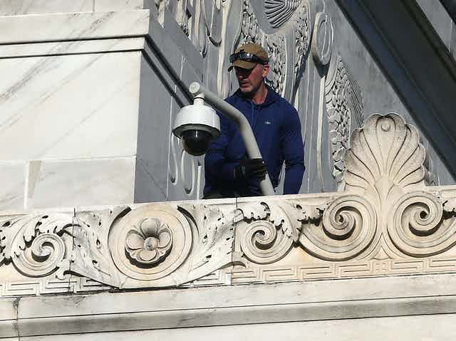 A man standing on a ledge on the exterior of a marble building holds a pole with a security camera at one end