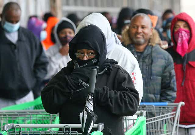 Shoppers clearly cold in their light jackets wait to get into a store. The woman in front has hood and scarf covering most of her face.